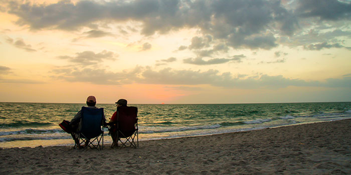 two people sitting on a beach during sunset
