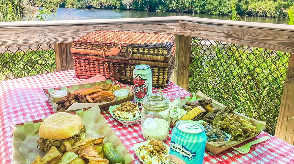 food on a picnic table with a picnic basket