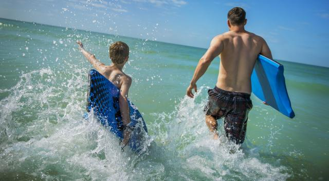 Dad and son run out to the surf of Siesta Key Beach