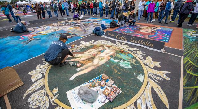 artist drawing on ground with chalk