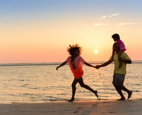 family running on a beach