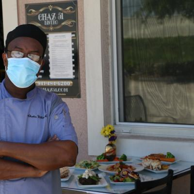 chef charles amherst standing with a mask on outside chaz 51 bistro in venice, florida
