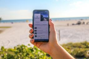 Hand holding a phone in front of Siesta Key Beach