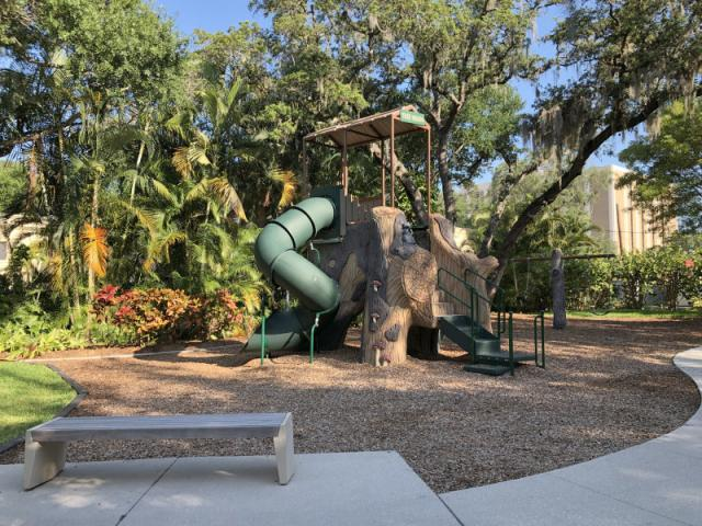 Laurel Park Playground - Includes a central tree trunk with two spiral slides and climbing areas. There is also a  swing set, sand box and grassy play area.
