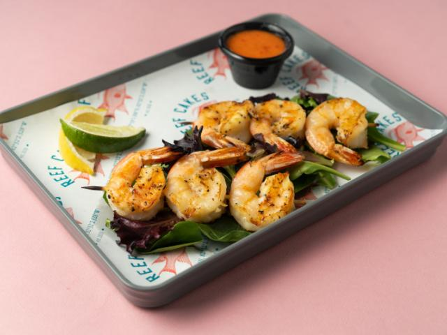 Grilled Shrimp Skewers - Half Dozen Seasoned Gulf Shrimp Expertly Grilled on a Bed of Spring Mix. Served with a Side of our Spicy Sweet Firecracker Sauce.