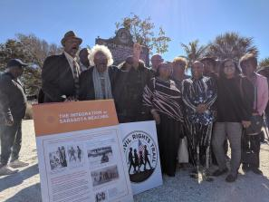 group of people standing near historical marker on lido beach in sarasota county florida