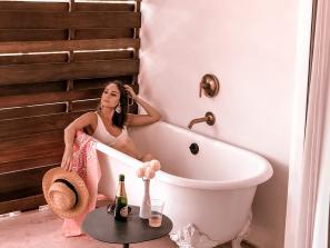 woman sitting in hotel bathtub outdoors