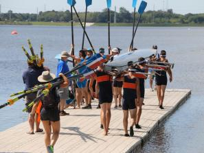Rowing teams walk down the dock at Nathan Benderson Park in Sarasota, Florida to prepare for a regatta race