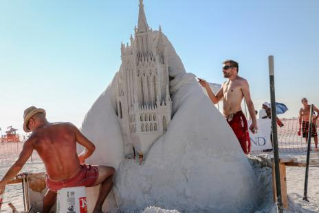 Two sand sculptors working on a sculpture on Siesta Key in sarasota florida