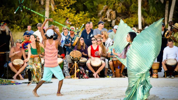 people dancing in a drum circle on siesta key beach