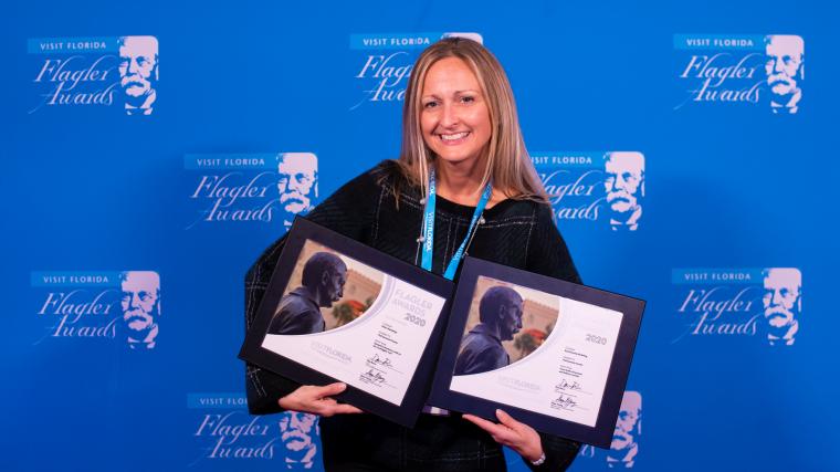 Erin Duggan, VP, holding two awards