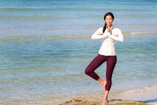 Woman doing yoga on the beach in sarasota