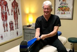 Man sitting up on a massage table showing leg stretch with yoga band