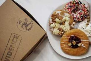 Three donuts next to a box that says Five-O donut company
