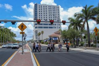 pedestrians walking across a crosswalk on tamiami trail in sarasota