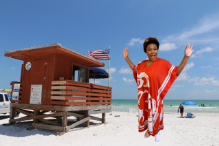 woman standing in front of a virtual beach background in sarasota florida