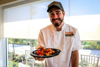 Chef holding out a plate of food from Placida Pearl in Florida