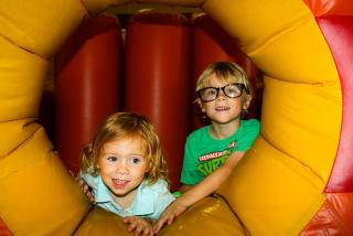 A very young boy and girl enjoying themselves at Bounce Down Under. Photo by Liz Sandburg