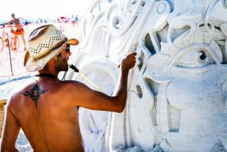 Sculptor carving a detailed design into sand on siesta key in florida