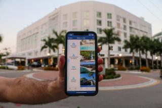 hand holding phone in front of a hotel in Sarasota, Florida