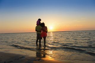 Family standing on shore during sunset at a Sarasota County beach