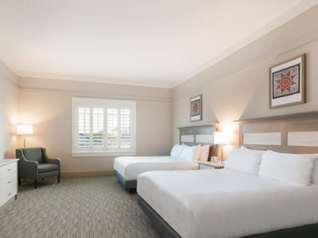 Standard Double Queen - Enjoy cozy beds, handcrafted details, quilts and one-of-a-kind décor. Our spacious Standard Double Queen Rooms include 2 Queen Beds, 1 small table with 2 chairs, separate dressing area and sink (most rooms have a walk-in shower, 8 of our rooms have bathtubs).