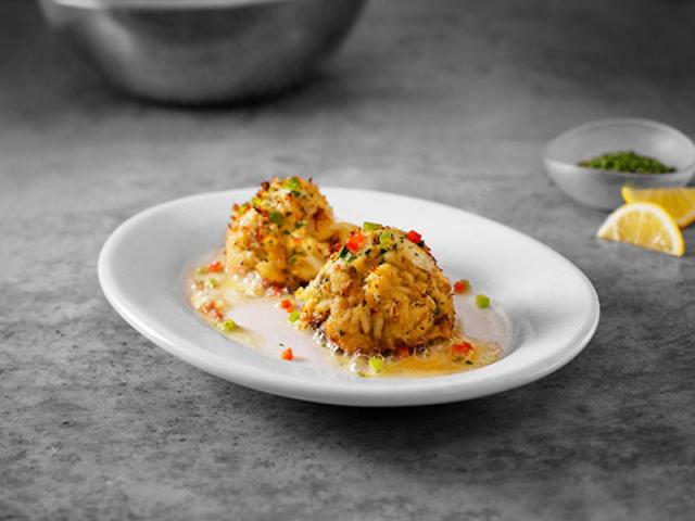 Sizzling Blue Crab Cakes - Served with lemon butter on a sizzling plate.