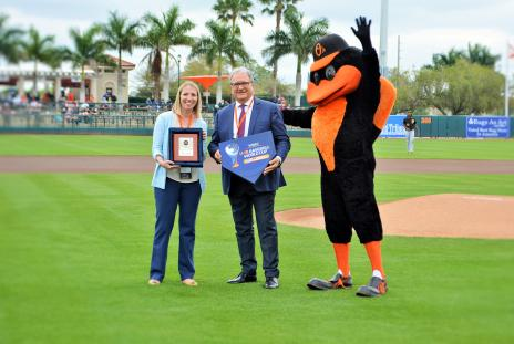 Shelby Connett displays plaque at Ed Smith Stadium in Sarasota