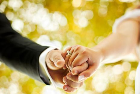 A bride and groom's hands locked together.