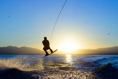 A wakeboarder performs a jump stunt against a setting sun
