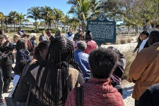 Participants gathered near the beach segregation historical marker at Lido Beach to reflect