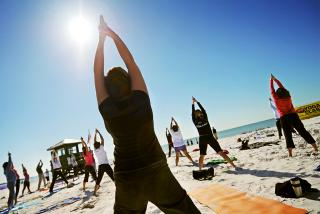 Group of women doing yoga on the beach in Sarasota